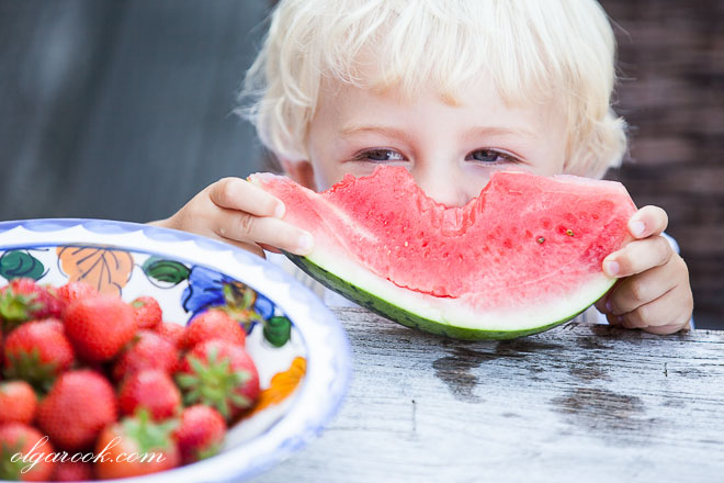 portrait of a little blond boy enjoying a watermelon.