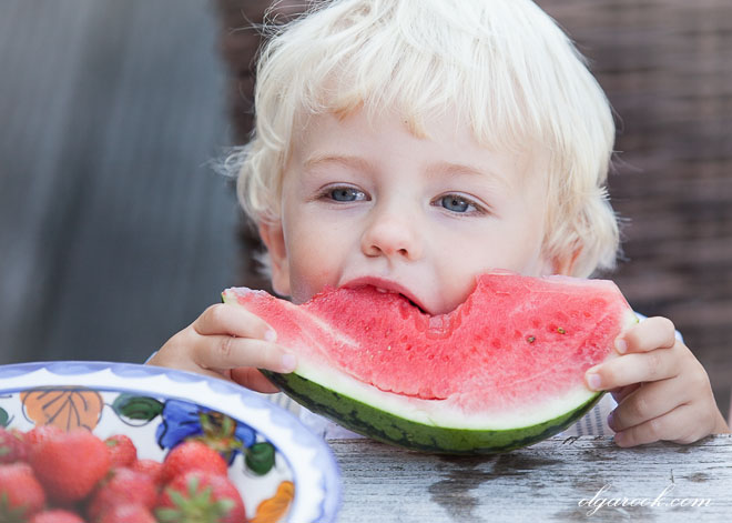 photo of a little boy eating a piece of melon.