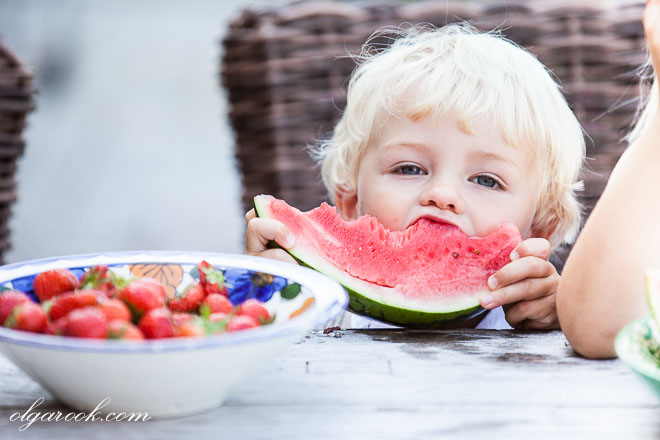 Photo of a little blond child eating watermelon in a funny way