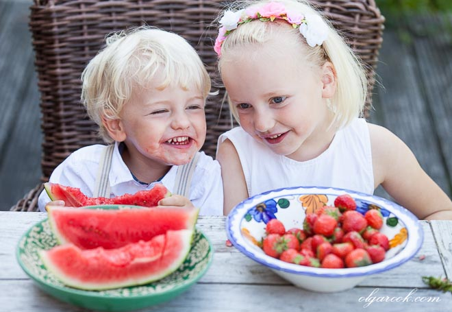 Portrait of two little children eating fruit at a garden table