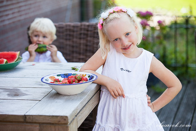 Photo of two little children at a garden table with dishes full of fruit.