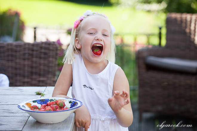 Funny photo of a little girl eating strawberries.