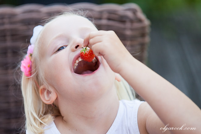 Photo of a little girl eating a strawberry