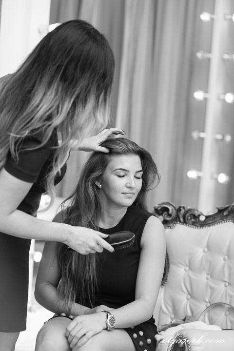 photo of a girl doing another girl's hair