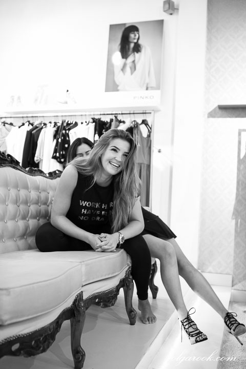 Photo of a laughing girl on a coach at a clothes boutique