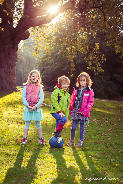 Photo of three children playing in an autumn park in the golden sunlight.
