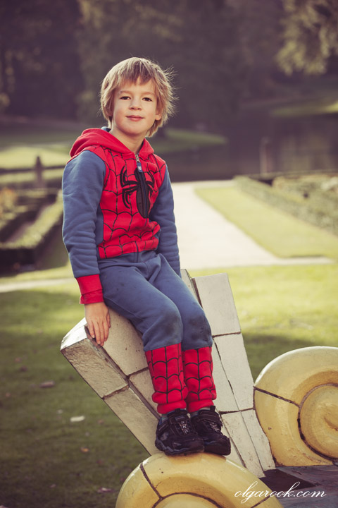 portrait of a little boy in a park wearing a Spiderman costume