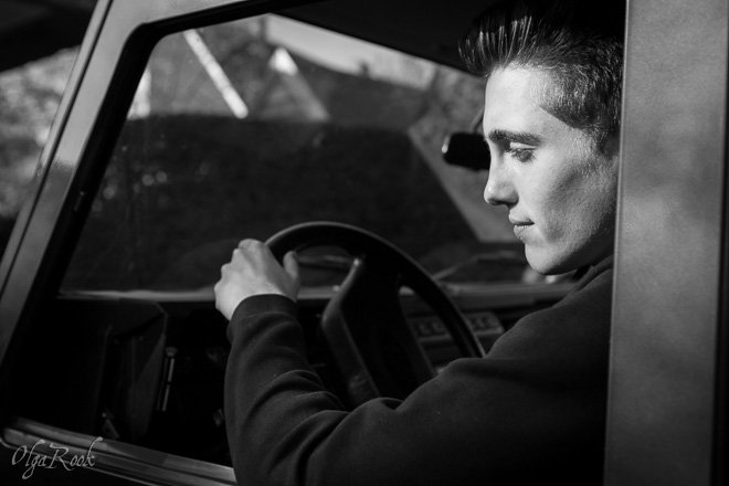 Portrait of a young man driving a car. The photo recalls the images of James Dean and the Hollywood road movies