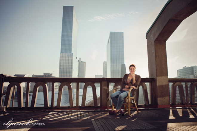 Business reportage of a young creative professional at a balcony with a view on the business centre of a city