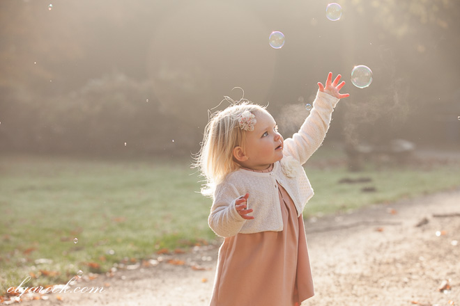 Chasing the dreams. Portrait of a little girl running after bubbles in a park. The photo is made during the golden hour and has a fairy tale atmosphere.