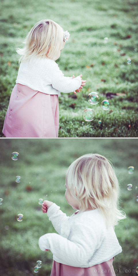 Dreamy photos of a blond little girl playing with soap bubbles in a grass field
