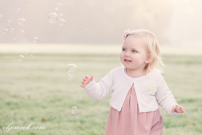 Portrait of a little girl chasing soap bubbles in a park
