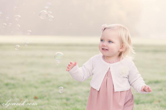 portret van een klein meisje die achter de zeepblazen in een veld rent