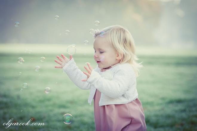 sprookjesachtig portret van een klein meisje die in een ochtenduur met de zeepblazen in een park speelt