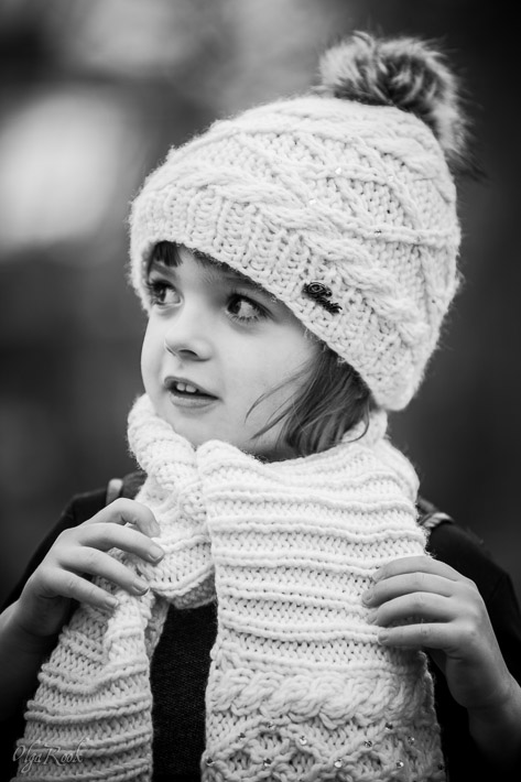 portrait of a little girl wearing a scarf and a winter hat