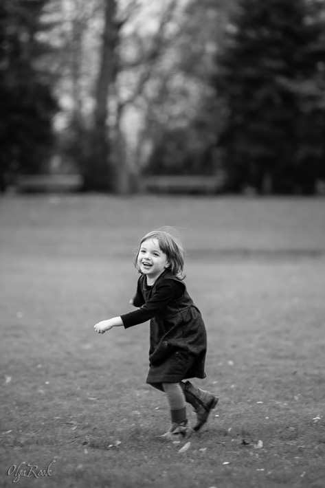 photo of a cheerful little girl running through a park