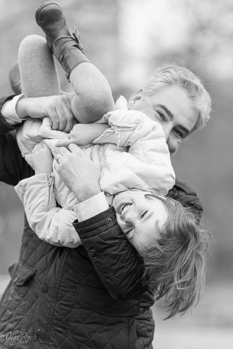 portrait of a father holding his small laughing daughter in the air
