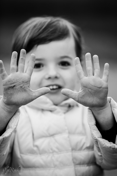 funny portrait of a small girl showing her dirty hands