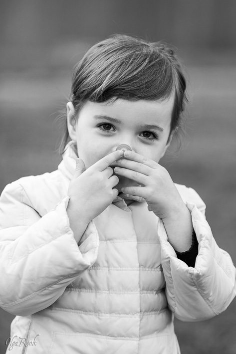 portrait of a little girl holding a sweet in front of her nose