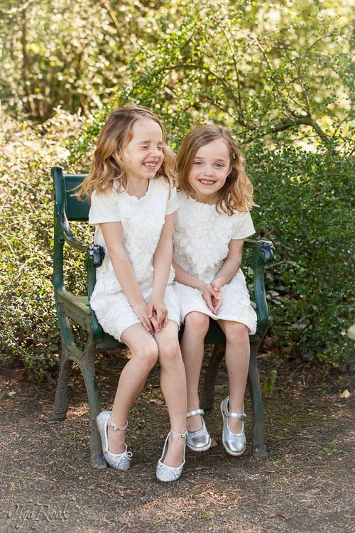 Vrolijk portret van tweeling zusjes in de tuin.
