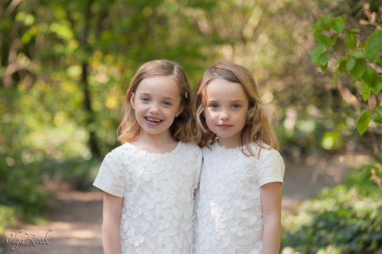 Portrait of little twin sisters in a spring park.