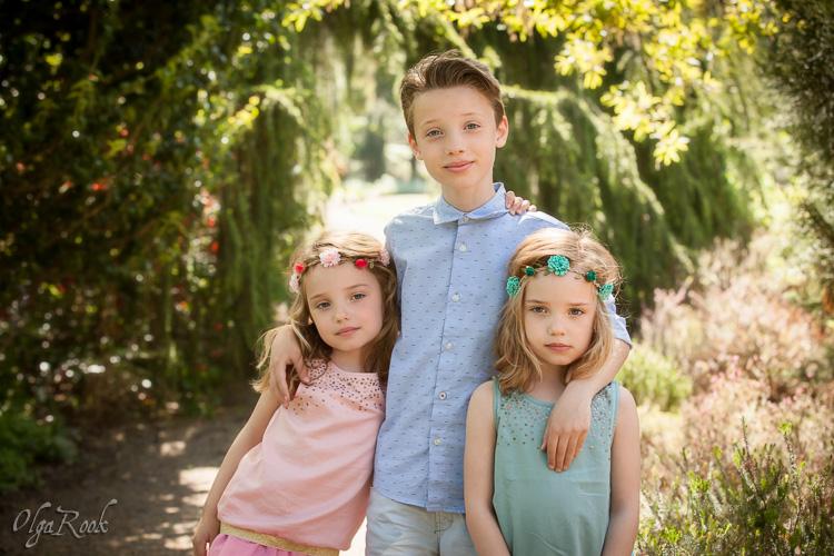Portret van tweeling zusjes met hun oudere broertje in een park.