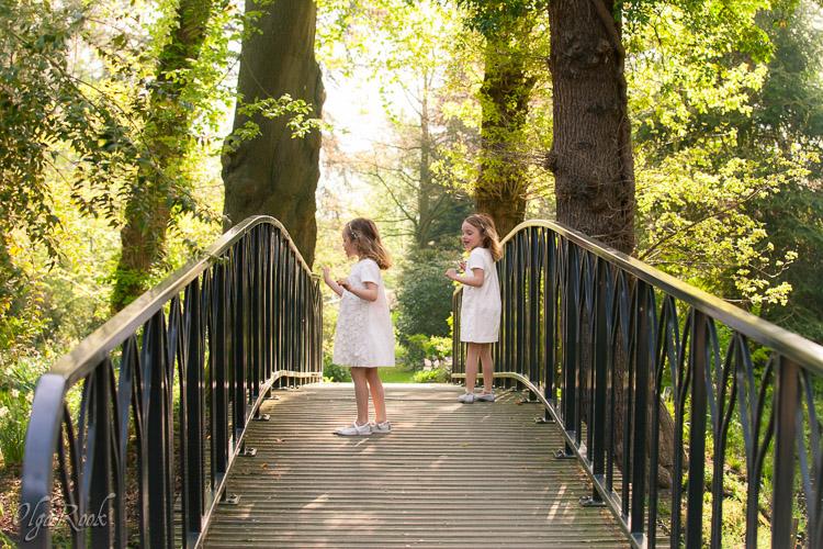 Foto van twee kleine meisjes die op een brug in een park lopen.