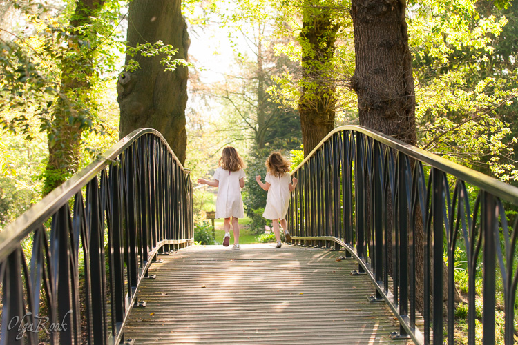 Poetic portrait of two little girls wearing white dresses and running along a bridge in a park