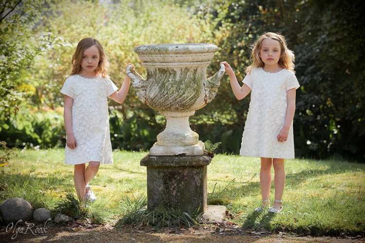 Klassieke en kleurrijke kinderportret: tweeling meisjes naast een antieke tuinvaas.