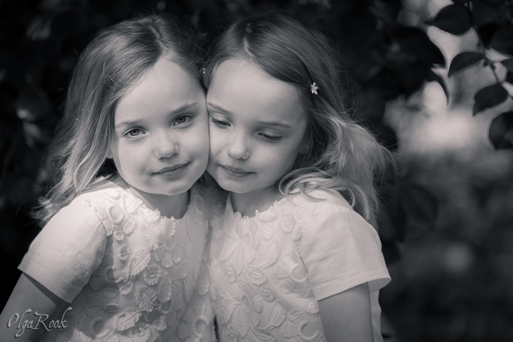 Classic and nostalgic monochrome portrait of two little twin sisters in a park.