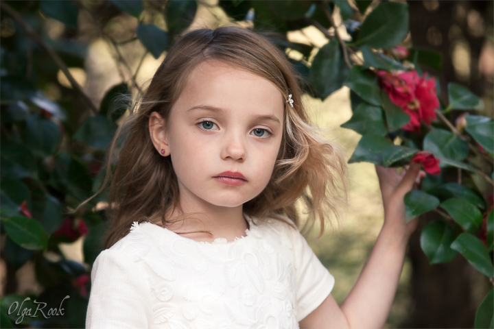 Classic and romantic portrait of a little girl standing next to a camellia tree.