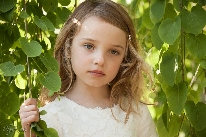 Dreamy and romantic portrait of a little girl standing between the branches of a green tree.
