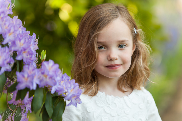 Romantic and gentle portrait of a little girl at a rhododendron tree in a park.