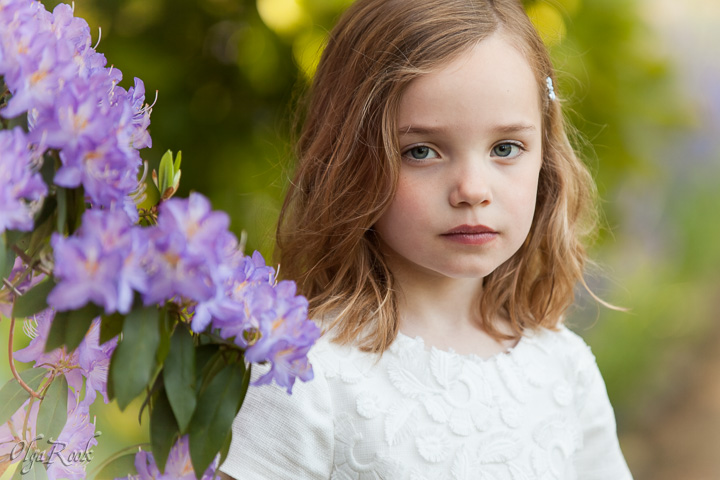 Dreamy and romantic portrait of a little girl standing by a lilac rhododendron. The colour combination and bokeh recalls a feel of a water-colour painting.