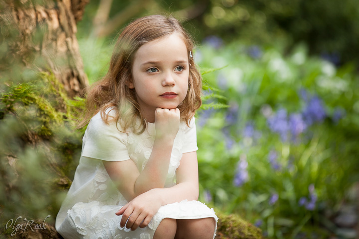 Fairy-tale child photography: a dreamy little girl is sitting in a garden or in the wood.