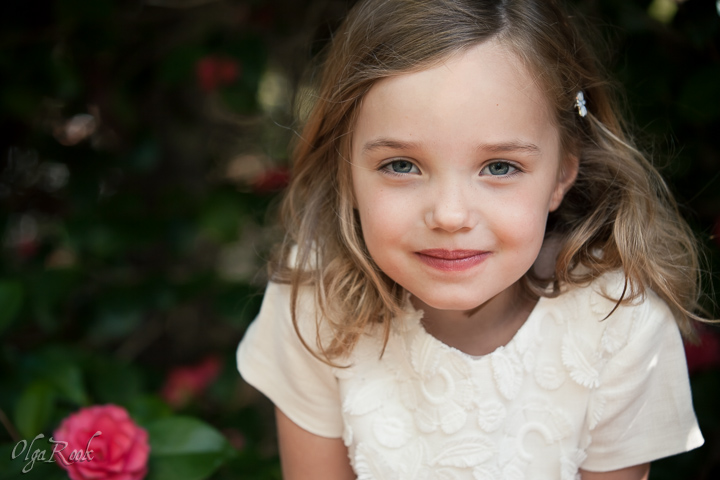 Portrait of a self-confident looking little girl standing in the shadow next to a camellia tree.