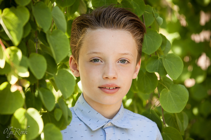 Classic and romantic portrait of a handsome young boy standing amongst the branches of a green tree in a park.