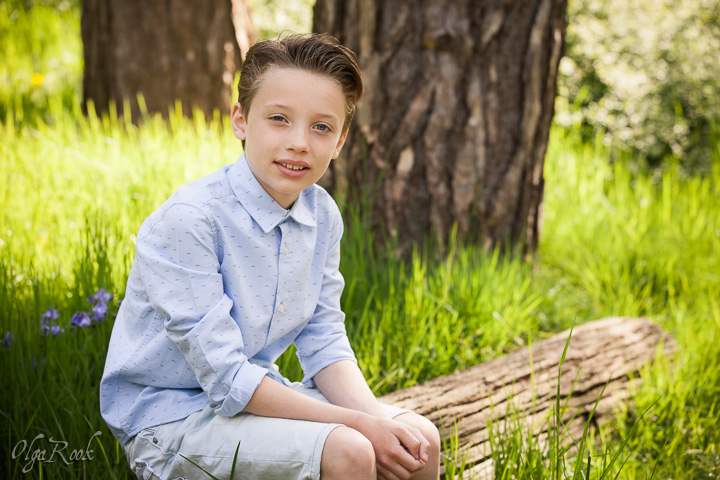 Portrait of a boy sitting on a log in a forest.