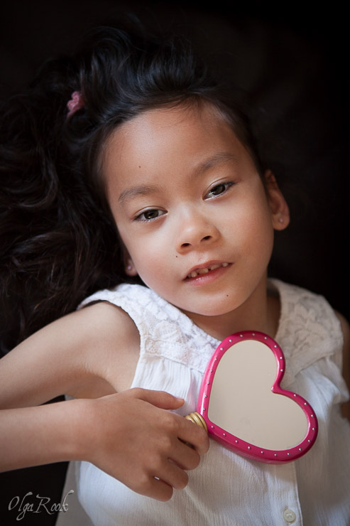 classic and nostalgic portrait of a little girl holding a heart-shaped toy mirror in her hand