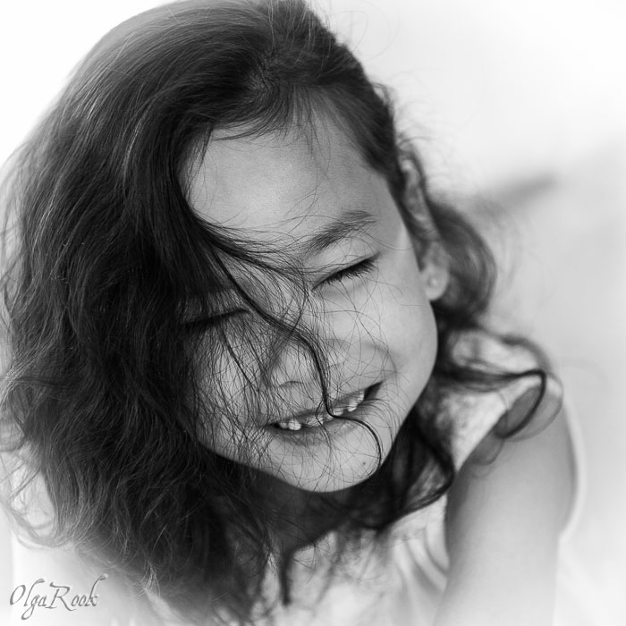 funny portrait of a laughing little girl with hair in front of her face