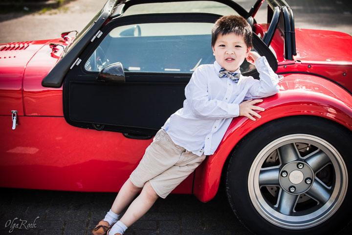 portret van een klein jongetje naast een rode sportauto