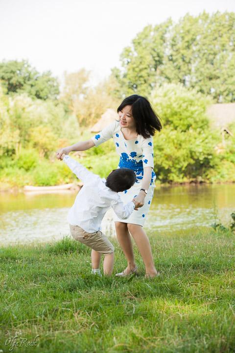 portret van een moeder en haar klein zoontje dansend op het gras in een zomers park
