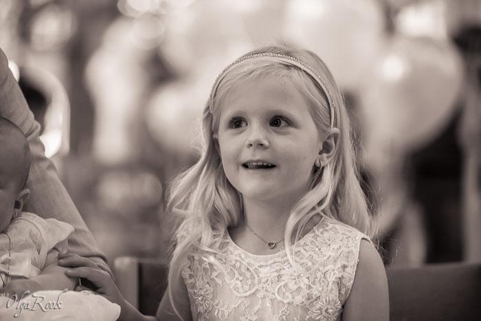 Een meisje met een stralend gezicht tijdens de doopceremonie