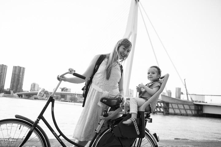 Portret van een moeder en een dochtertje op een fiets naast de Erasmusbrug in Rotterdam