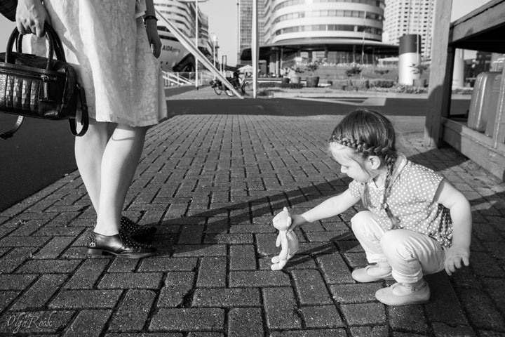 foto van een klein meisje dat op een straat in Rotterdam zit te spelen