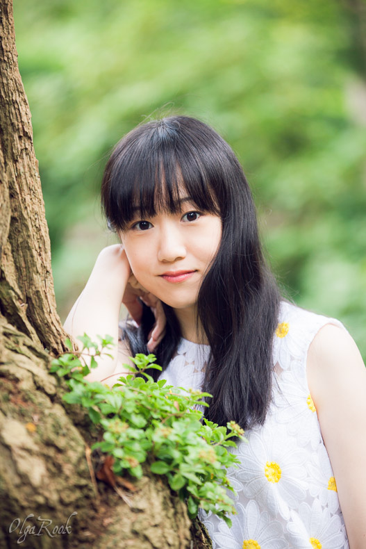 portrait of a girl leaning against a tree: she has a dreamy look and a gentle smile