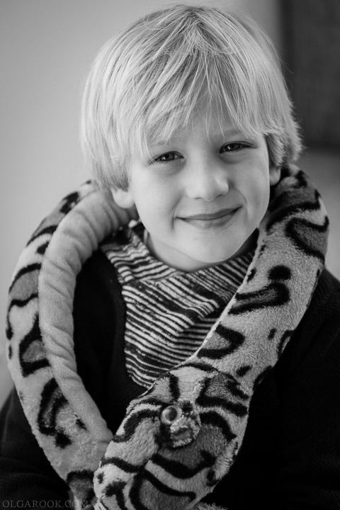 fotoportret thuis: een klein jongetje met een knuffel slang