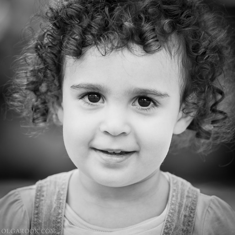 black and white outdoor portrait of a cheerful curly little girl