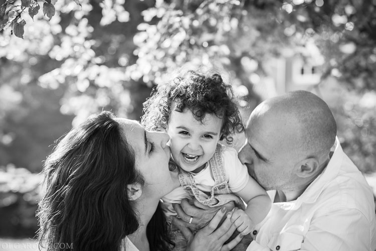 spontaneous and fun family portrait of parents with their little daughter in a park