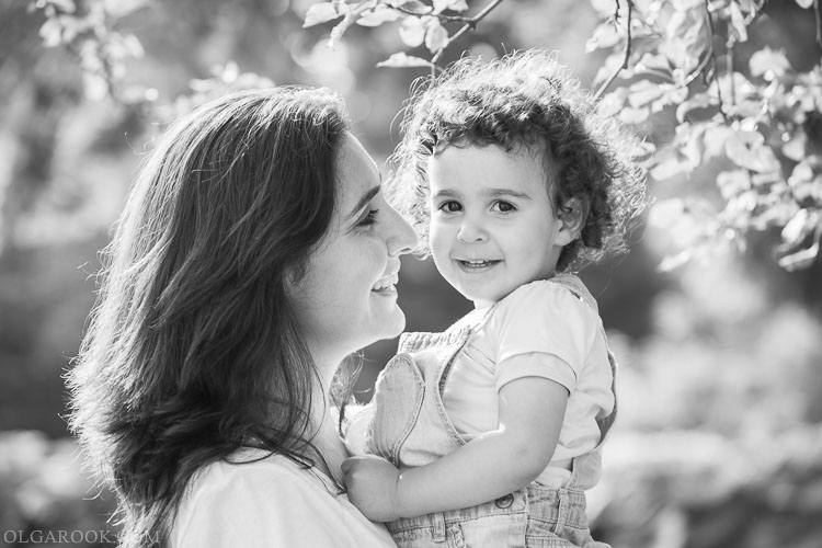 Mother and daughter photography: an emotional portrait of a beautiful mother holding her little daughter in her hands in a sunny park
